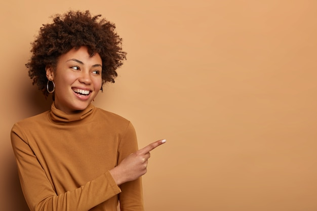 Blije vrouw met donkere huid en afro-haar wijst met wijsvinger opzij naar advertentie of grafiek, vertelt buitengewoon goed nieuws, suggereert de beste deal ooit, ziet favoriete product in de winkel, draagt coltrui