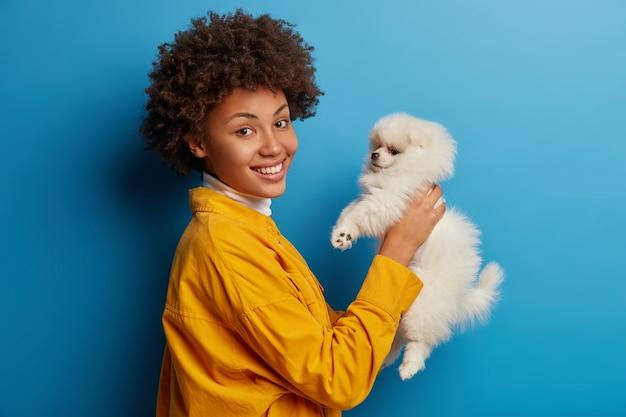 Blije vrouw met een donkere huidskleur, tevreden met een goede fokkerij van huisdieren