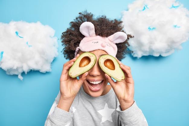 Blije vrouw met krullend haar bedekt ogen met avocadohelften raadt aan om natuurlijke biologische cosmetica te gebruiken, gekleed in nachtkleding, slaapmasker op voorhoofd geïsoleerd over blauwe muur
