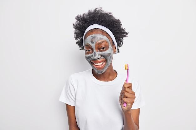 Blije vrouw met krullend haar brengt voedend kleimasker aan glimlacht breed verzorgt tanden