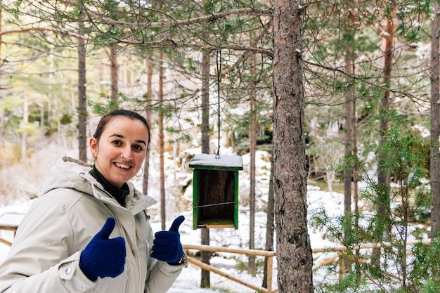 Blije vrouw omdat ze net een houten vogelnest in het bos heeft geplaatst. besneeuwde landschap