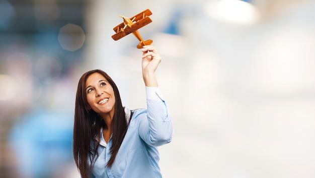 Blije vrouw spelen met een stuk speelgoed vliegtuig