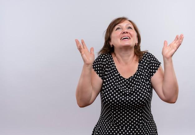 Blije vrouw van middelbare leeftijd die met opgeheven handen op geïsoleerde witte muur met exemplaarruimte omhoog kijkt