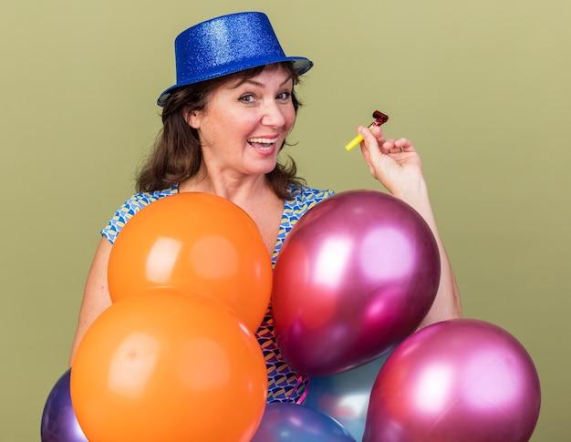 Blije vrouw van middelbare leeftijd in feestmuts met een bos kleurrijke ballonnen die een fluitje vasthoudt en vrolijk glimlacht