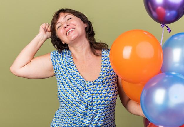 Blije vrouw van middelbare leeftijd met een stel kleurrijke ballonnen die de vuist blij en opgewonden opheft