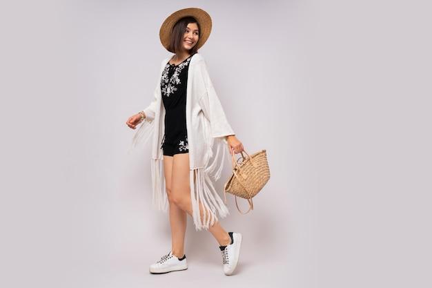 Blije vrouw van volledige lengte met kort kapsel in stijlvolle boho zomeroutfit. strohoed en tas.