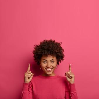 Blije vrouw wijst met beide vingers op kopie ruimte hierboven, heeft vriendelijke positieve glimlach, draagt lichte kleding in één toon met ruimte