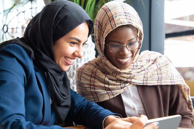 Blije vrouwelijke collega's die op inhoud op telefoon letten