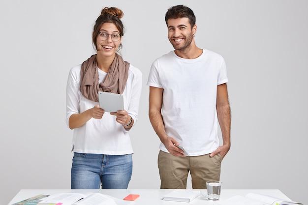 Blije vrouwelijke en mannelijke studenten toekomstige architecten, moderne technologie gebruiken voor werk, aan tafel staan met de nodige papieren, blije uitdrukkingen hebben, klaar om de voorbereiding op het seminarie te starten