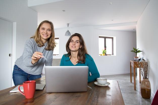 Blije vrouwelijke klanten die online winkelen genieten van