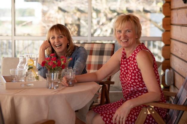 Blije vrouwelijke vrienden die een gesprek hebben, aan de tafel met wit tafelkleed