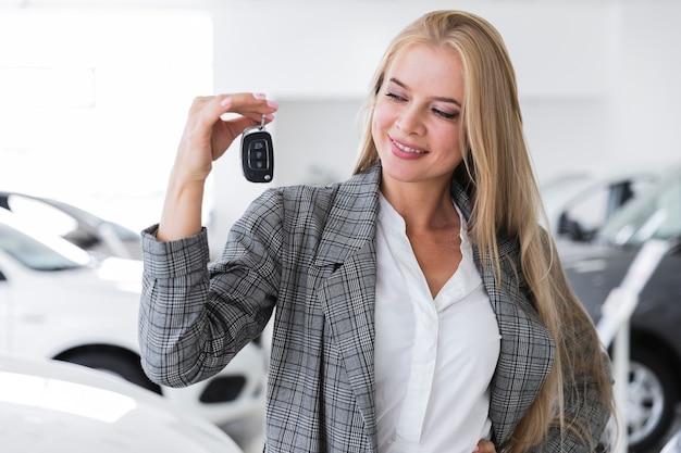 Blije vrouwen die sleutels middelgroot schot bekijken