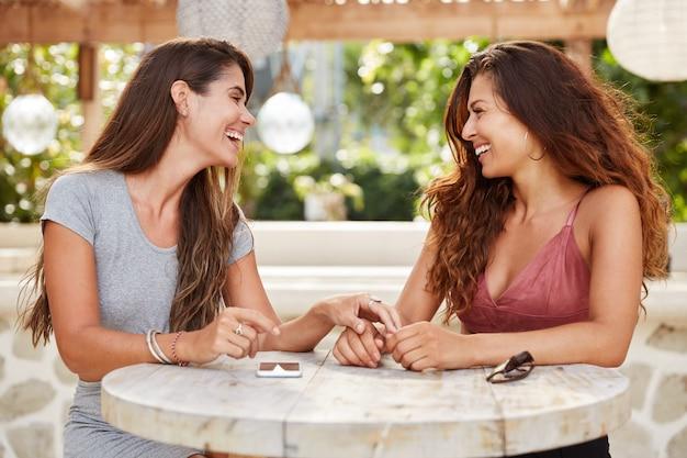 Blije vrouwen met donker luxueus haar, ontmoeten elkaar in een gezellige koffieshop, genieten van een rustige sfeer en intimiteit