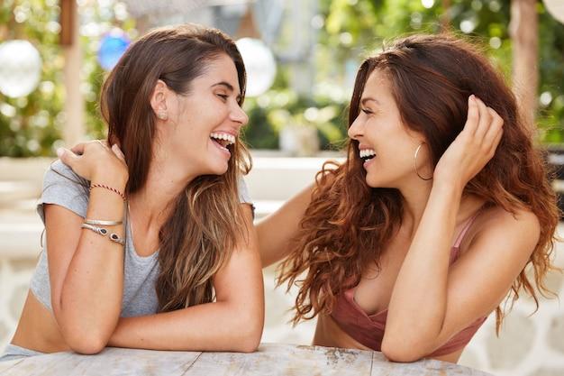 Blije vrouwtjes met een aantrekkelijk uiterlijk, kijken elkaar vreugdevol aan, glimlachen gelukkig