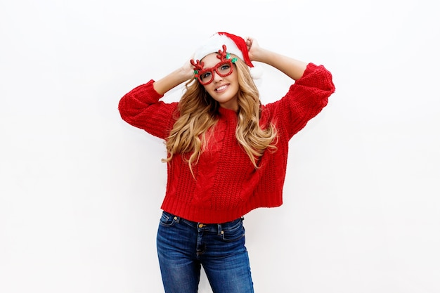 Blije zorgeloze blonde vrouw in schattige maskeradeglazen en nieuwe jaarhoed in het rode gebreide sweater stellen