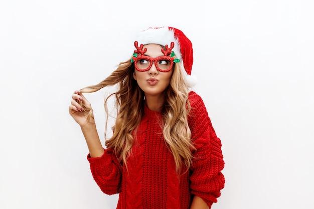 Blije zorgeloze blonde vrouw in schattige maskeradeglazen en nieuwe jaarhoed in rode gebreide trui die zich voordeed op witte muur. isoleren. kerstmis en nieuw testfeestconcept.