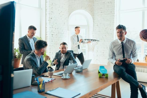 Blije, zorgeloze collega's die plezier hebben op kantoor terwijl hun collega's hard en geconcentreerd werken.