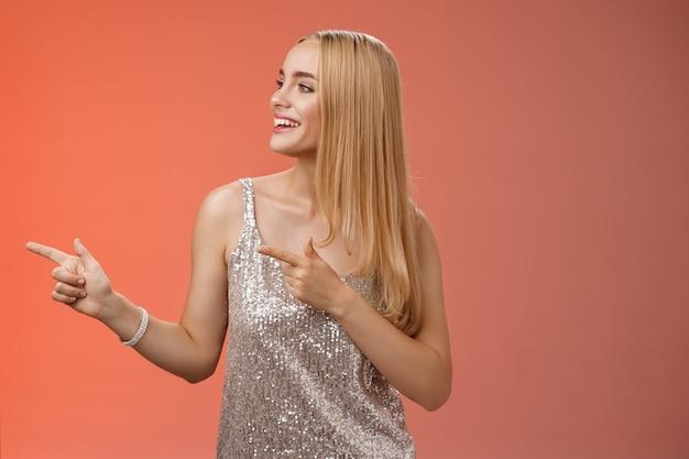 Blije zorgeloze jonge rijke glamour blonde vrouw in glinsterende zilveren jurk genieten van geweldig feest dansen draaien wijzend links glimlachend breed wachten vriendin brengen drankjes, rode achtergrond.