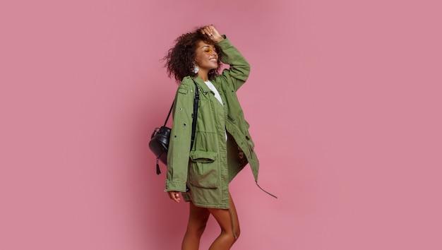 Blije zwarte die pret in studio over roze achtergrond heeft. wit t-shirt, groen jasje. stijlvolle lentelook.