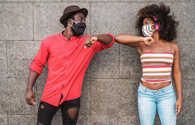 Blije zwarte vrienden die beschermende maskers dragen terwijl ze hun ellebogen stoten in plaats van te begroeten met een knuffel - focus op gezichten