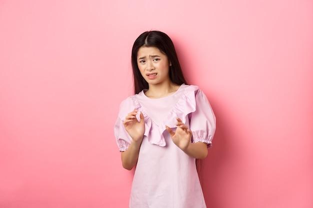 Blijf bij me uit de buurt. weerzinwekkend aziatisch meisje dat handen opheft om iemand te blokkeren, ineenkrimpt van afkeer, terughoudend kijkt en vraagt om te stoppen, iets slechts afwijst, roze achtergrond.
