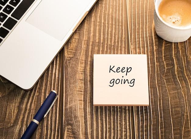 Blijf doorgaan sticker in de werkruimte met laptop en koffie