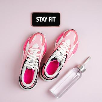 Blijf fit. nieuwe sneakers en smartphone op een roze achtergrond. app om binnen te trainen.