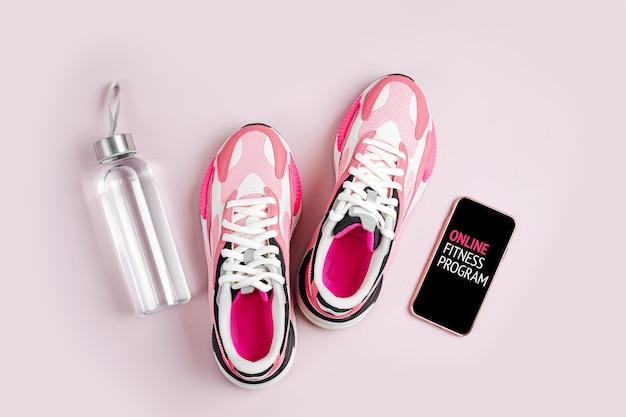 Blijf fit. nieuwe sneakers en smartphone op een roze achtergrond. online fitnessprogramma.