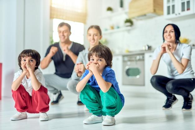 Blijf fit, schattige latijns-amerikaanse jongens die samen met hun ouders en zus sporten bij