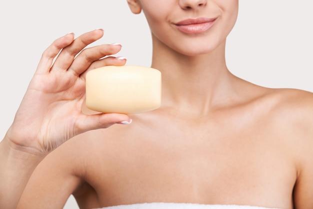 Blijf fris en schoon. bijgesneden afbeelding van mooie jonge vrouw gewikkeld in een handdoek met een stuk zeep in haar hand terwijl ze tegen een grijze achtergrond staat