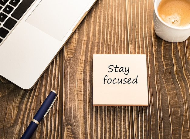 Blijf gefocust sticker in de werkruimte met laptop en koffie