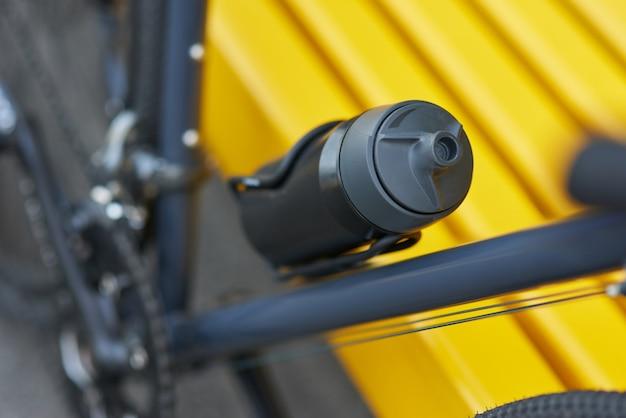 Blijf gehydrateerd close-up shot van zwarte aluminium waterfles op fiets selectieve focus