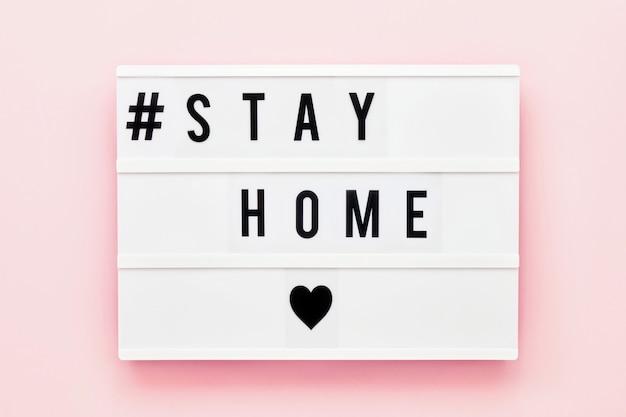 Blijf huis geschreven in lichtbak op roze achtergrond. gezondheidszorg en medisch concept. bovenaanzicht. quarantaine concept.