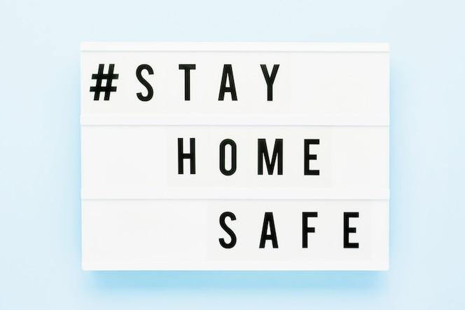 Blijf huis veilig geschreven in lichtbak op blauwe achtergrond. gezondheidszorg en medisch concept. bovenaanzicht. quarantaine concept.