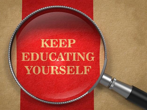 Blijf jezelf onderwijzen - slogan. vergrootglas op oud papier met rode verticale lijn achtergrond.