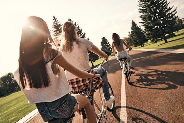 Blijf kalm en rij door. achteraanzicht van jonge mensen in vrijetijdskleding die samen fietsen terwijl ze zorgeloze tijd buitenshuis doorbrengen
