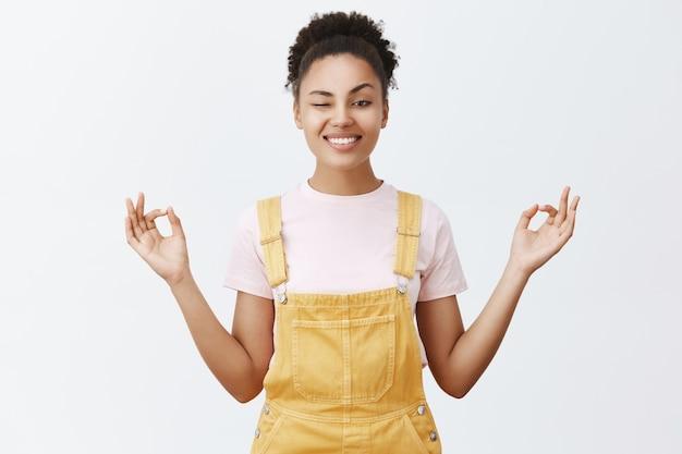 Blijf kalm en vrij van stress met meditatie. vrolijke en speelse stijlvolle moderne afro-amerikaanse vrouw in gele overall, gluren met één oog en breed glimlachend, hand in hand in zen pose