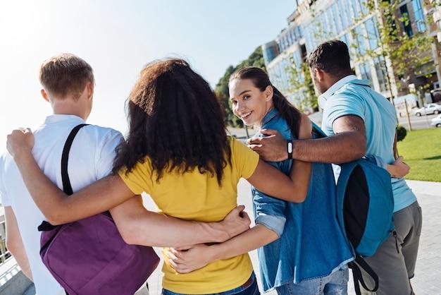 Blijf lachen. charmant meisje positiviteit uitdrukken en haar vrienden omhelzen terwijl het hoofd draaien