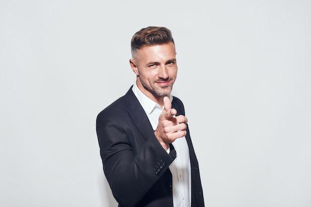 Blijf positief portret van vrolijke bebaarde zakenman in klassiek pak gebaren en glimlachen terwijl