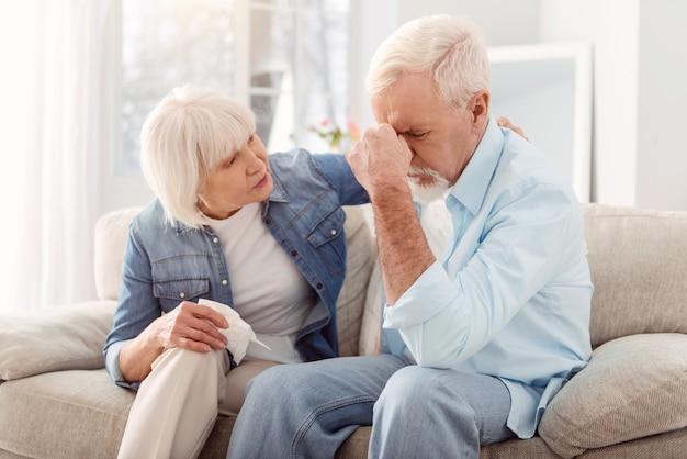 Blijf rustig. zorgzame bejaarde vrouw streelde haar man terug en troostte hem terwijl hij huilde, van streek zijn door het verlies van zijn vriend