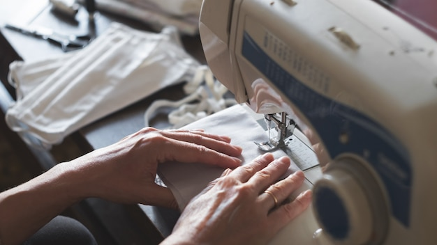Blijf thuis. beschermende antivirusmaskers naaien. vrouw naait maskers op een naaimachine