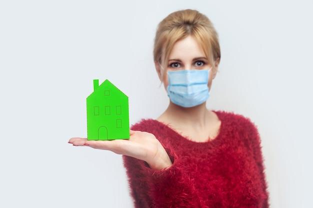 Blijf thuis, blijf veilig. quarantaine tijd. portret van een jonge vrouw met een chirurgisch medisch masker in een rode blouse die staat, met een klein huis van papier. binnen, geïsoleerd, studio-opname op grijze achtergrond