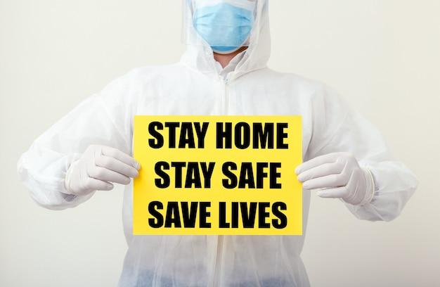 Blijf thuis blijf veilig save lives-tekst op geel waarschuwingsbord in handen van de arts. coronavirus, covid-19 zelfquarantaine-isolatie. medisch, gezondheidszorg sociaal afstandsconcept.