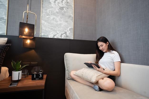 Blijf thuis concept een meisje met het witte t-shirt zittend op de gezellige grote bank in een goed ingerichte woonkamer.