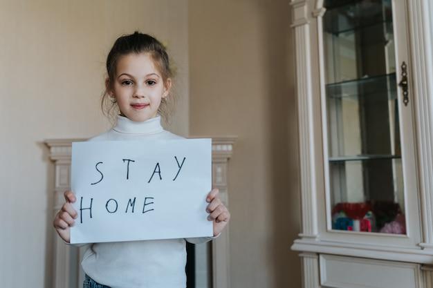 Blijf thuis concept. het kleine teken die van de meisjesholding zeggen thuis blijven voor virusbescherming en hun gezondheid van covid-19 behandelen.