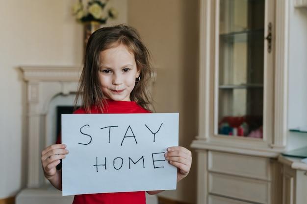 Blijf thuis concept. klein meisje in het rode teken van de t-shirtholding die thuis blijven houden voor virusbescherming en zorg voor hun gezondheid van covid-19. quarantaine concept.