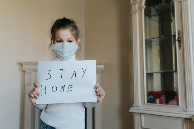 Blijf thuis concept. klein meisje in het teken van de maskerholding zegt thuisblijven voor virusbescherming en zorg voor hun gezondheid van covid-19. quarantaine concept.