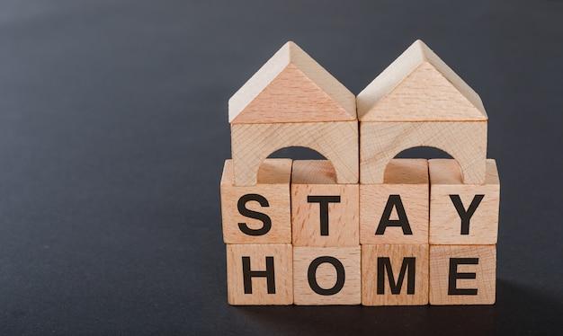 Blijf thuis concept met houten kubussen, houten speelgoed huis op grijs.