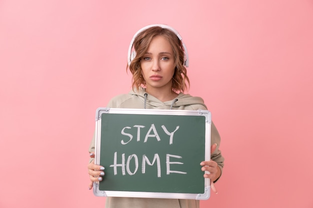 Blijf thuis concept vrouw met koptelefoon gekleed oversized hoodie houdt schoolbord met de woorden thuis blijven. bescherming tegen coronavirus nieuw normaal concept covid19 pandemie social distancing thuiswerken
