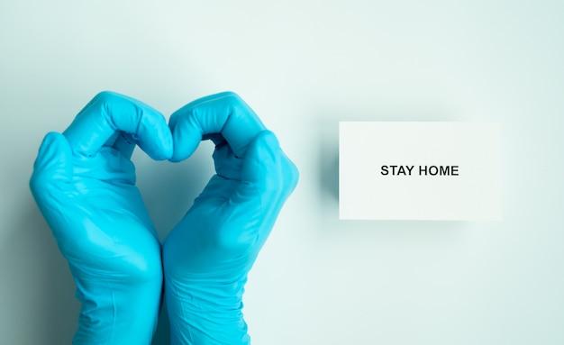 Blijf thuis en gezond om covid-19-verspreidingscampagne te voorkomen, tekst op papier met hartvormige handen van arts die blauwe handschoenen draagt
